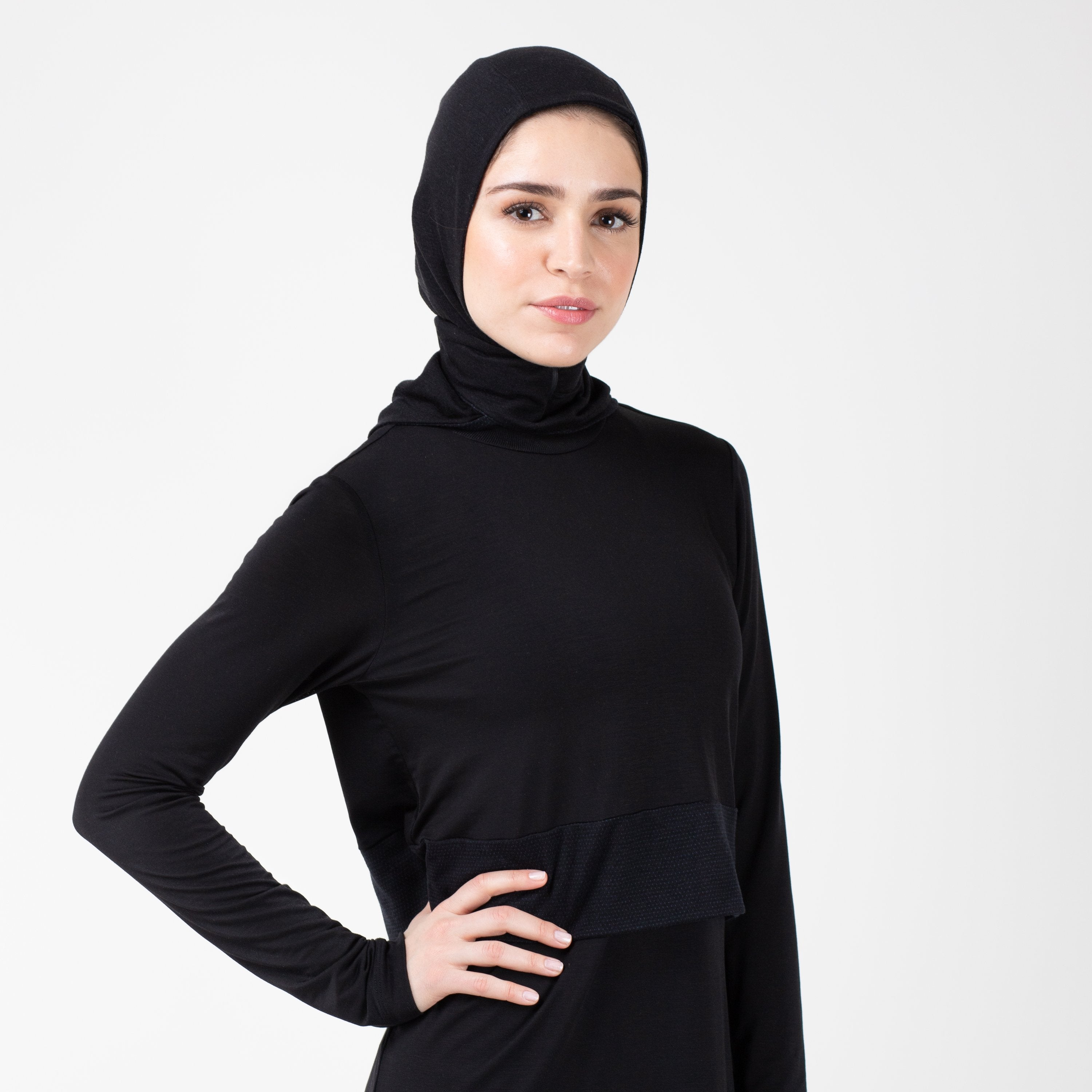 Woman facing right in a black shirt with a matching black HAWA hijab with her right hand on her hip.