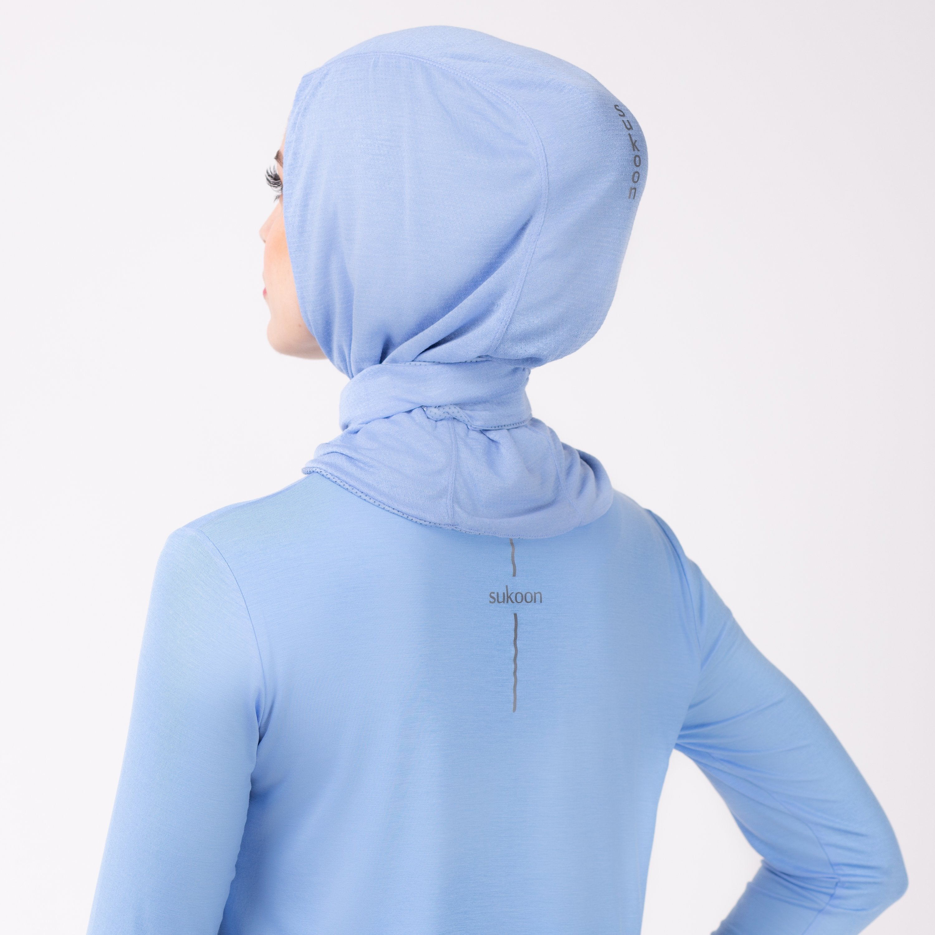 Back detail of a woman in a sky blue shirt with a matching sky blue HAWA hijab.