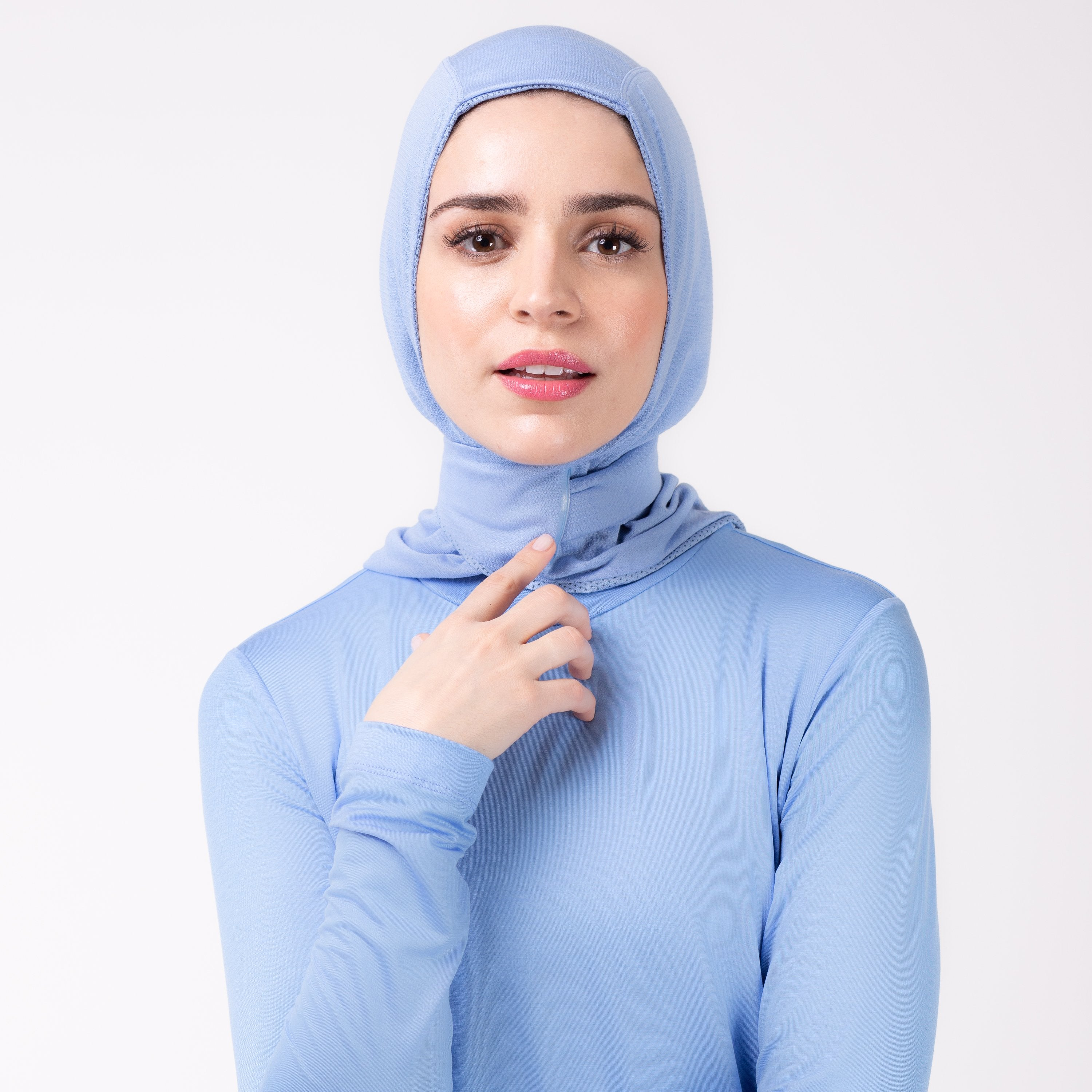 Front detail of a woman in a sky blue shirt with a matching sky blue HAWA hijab, touching the closure with her right hand.