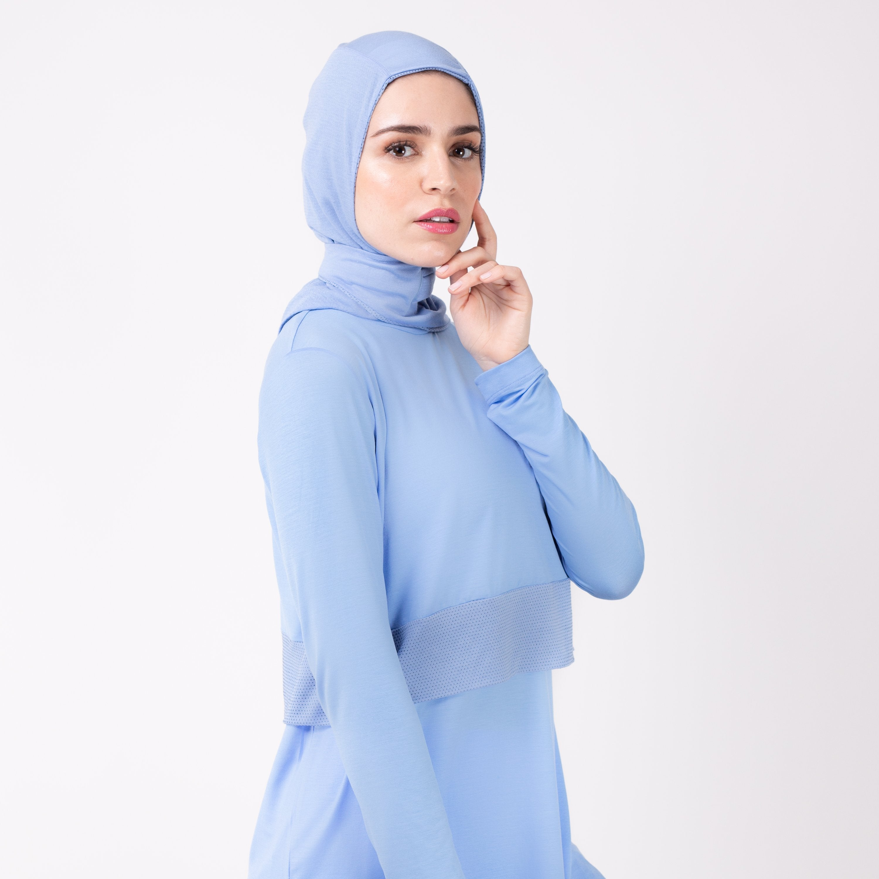 Woman facing right in a sky blue shirt with a matching sky blue HAWA hijab, touching her face with her left hand.