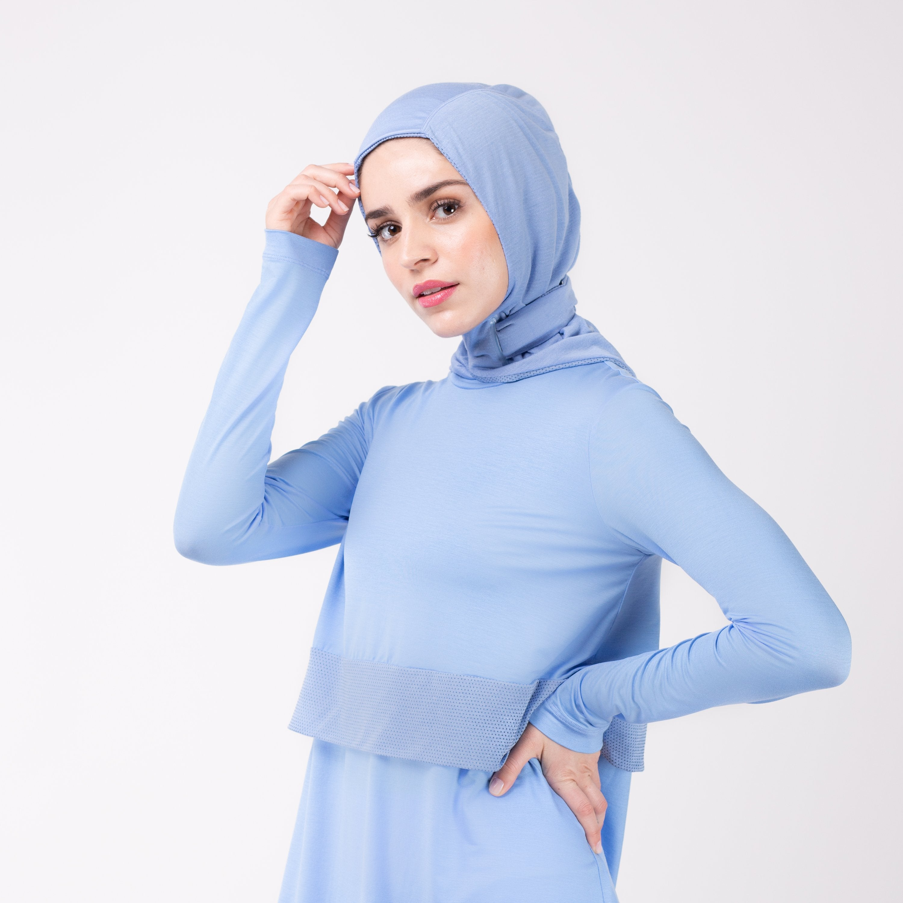 Woman facing left in a sky blue shirt with a matching sky blue HAWA hijab, touching the hijab fabric with her right and and her left hand on her hip.