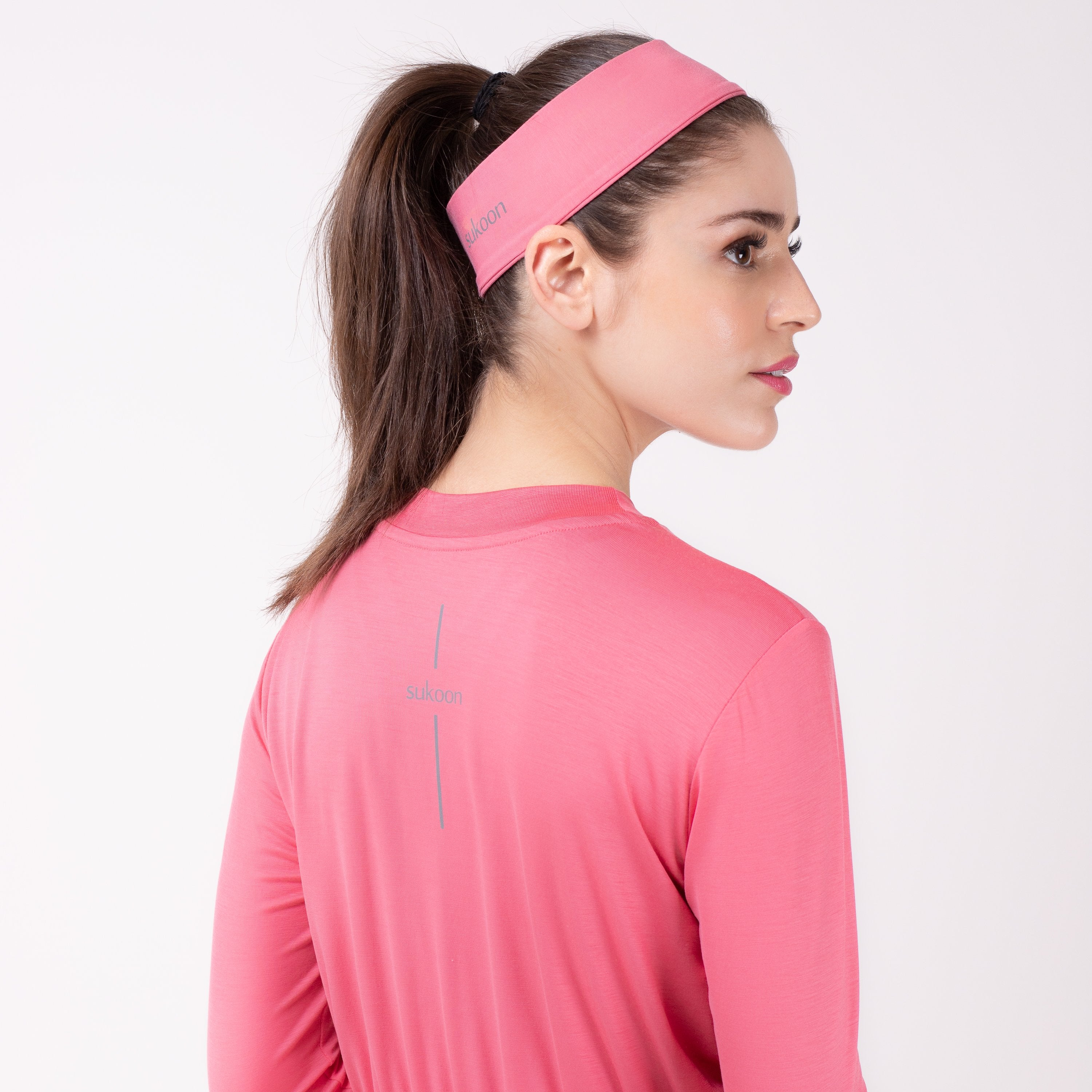 Back detail of woman in pink shirt with matching pink HAWA headband.