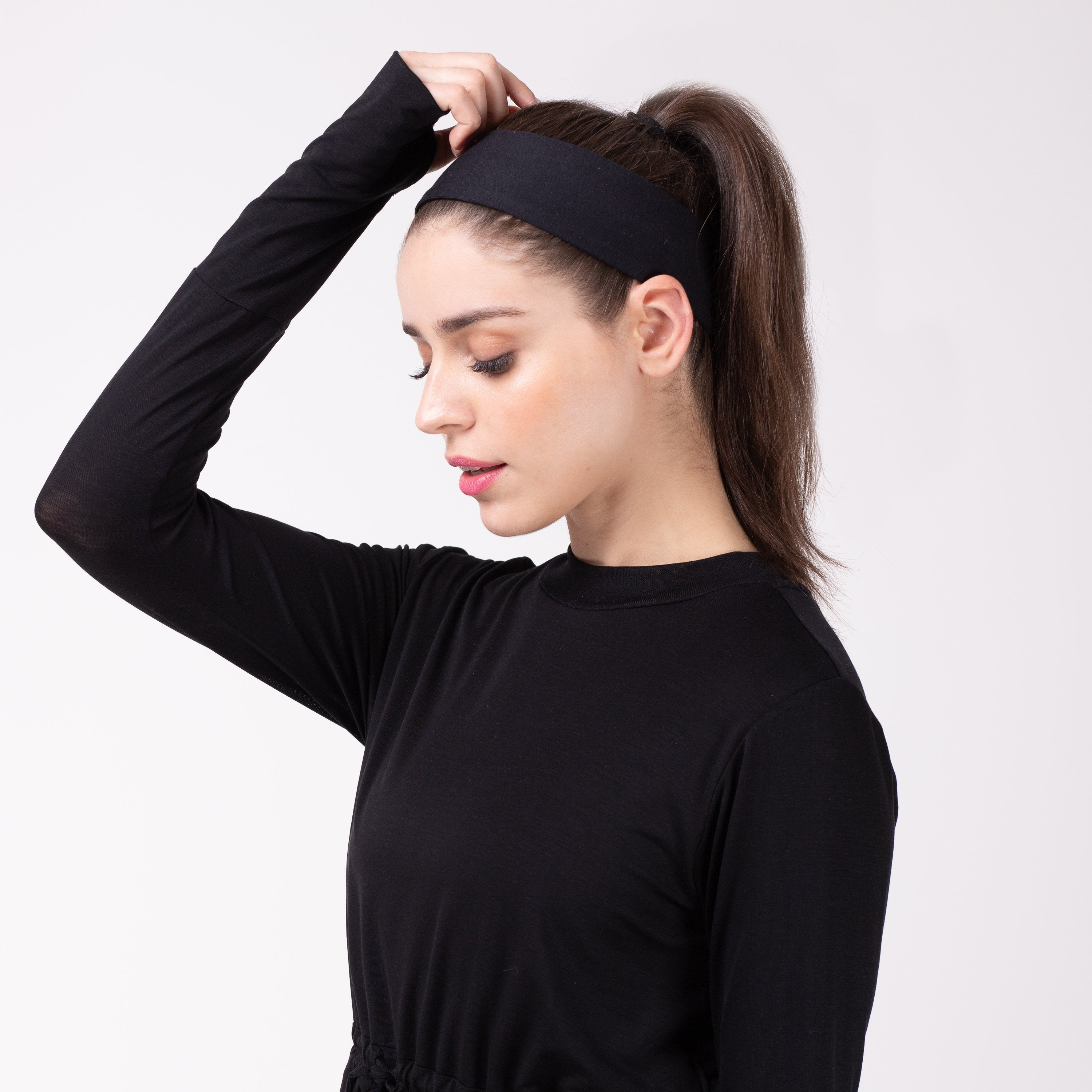 Woman looking left in black shirt with matching black HAWA headband.