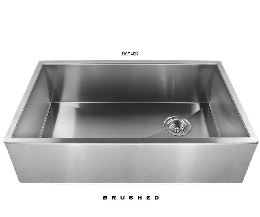 Brushed Stainless steel farmhouse apron front sink with a brushed finish. Handcrafted from 16 gauge stainless steel and installed under red quartz.