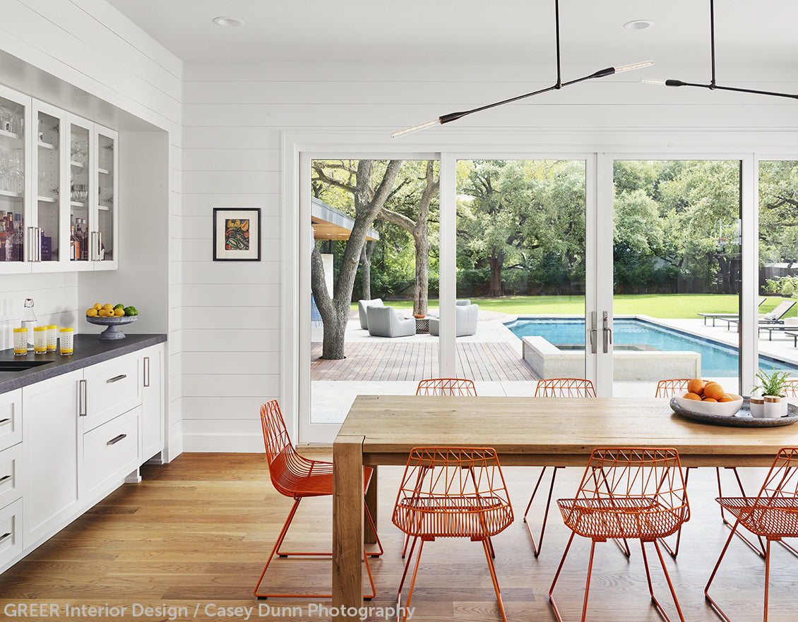 A wood kitchen table with orange chairs and two linear pendant lights above in Oil Rubbed Brass by Studio DUNN