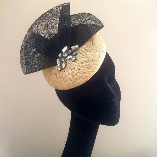 The perfect cocktail hat - a reversible ivory base with black trim and silver crystals.