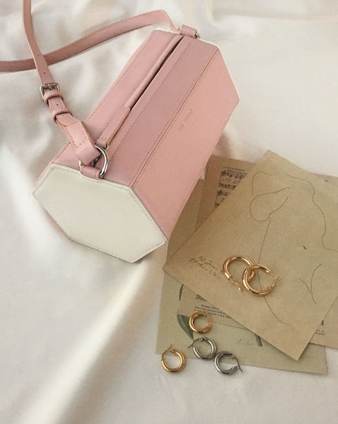 Hexagon shape prism cross-body bag featuring smooth, dusty pink and contrasting white leather - The Hexad Bags