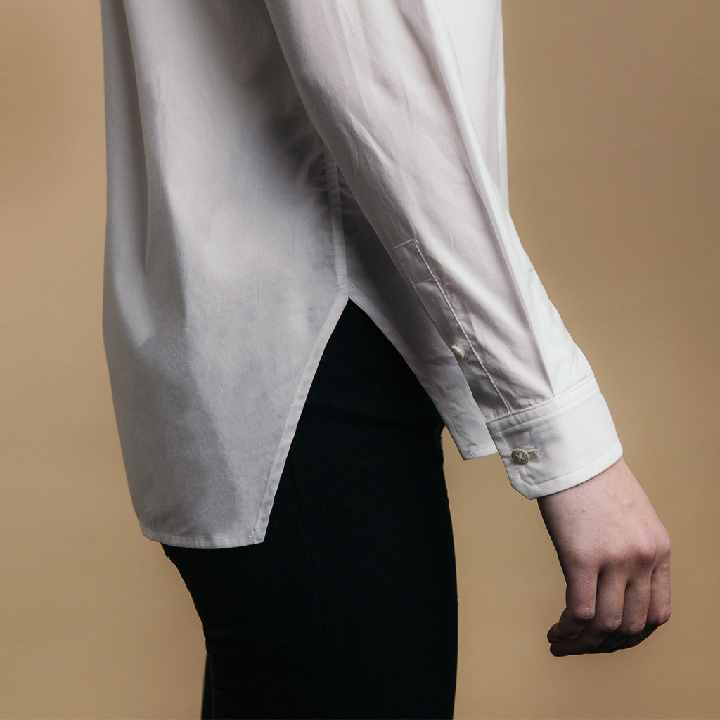 The Trapezoid Shirt - Paper White. Side view, angled hem meets at point.