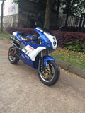 Venom Super Pocket Bike x19 Pocket Rocket 110cc in blue and white yamaha edition color combo facing forward with front headlights, gold monster handle bars, and big side view mirrors