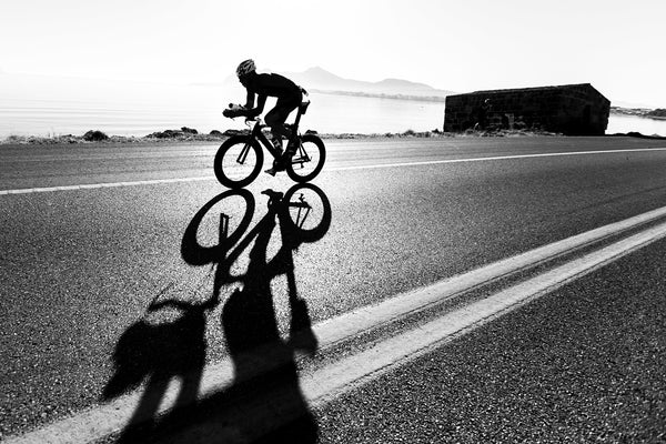 back and white image of cyclist training on-road