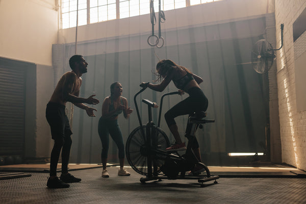 Two coaches training a female cyclist indoors