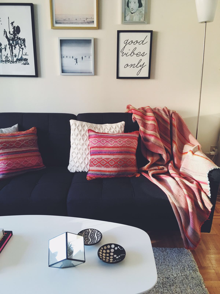 Apartment decoration, dark sofa with bright pillows and bright Peruvian frazada used as a sofa throw.