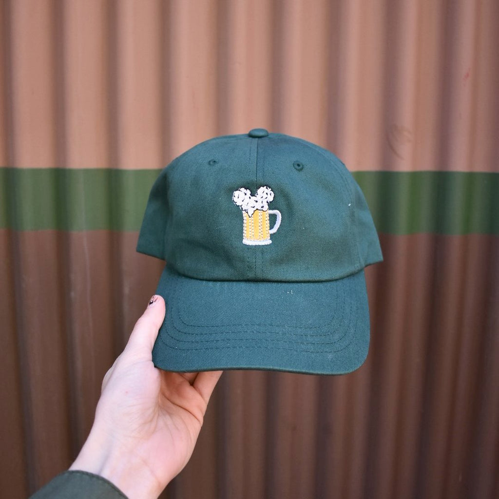 Our Mouse Ears and Cold Beers design has been condensed to show just the beer stein and the mouse ear beer foam on a forest green dad hat. This color is perfect to match the wilderness aesthetic of California Adventure or the Wilderness Lodge. However, it is also a great match for wearing on St. Patrick's Day.