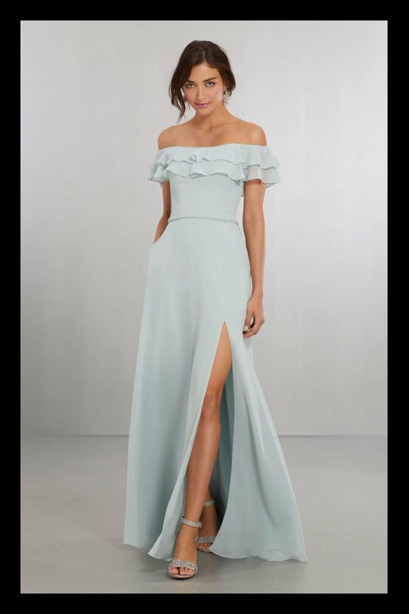 Model wearing a long dress with off the shoulder flounce, beaded waist belt and front split in sage green