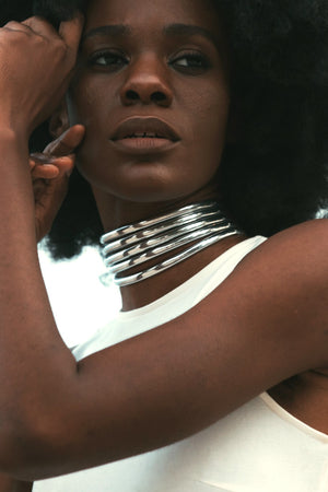 Close up of woman in a white dress posing with the Silver Ndebele Choker
