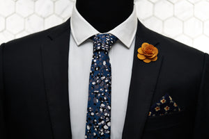 A men's suit jacket displays Dear Martian acessories, which include a floral patterned pocket square, orange flower lapel pin, and the Crooke blue steel spotted cotton tie.