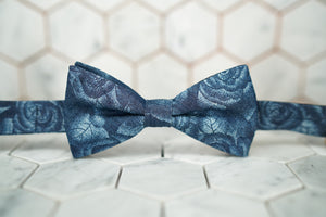 A front view of the Cranford rose denim bow tie by Dear Martian; the bow tie has light blue roses laid across its canvas.