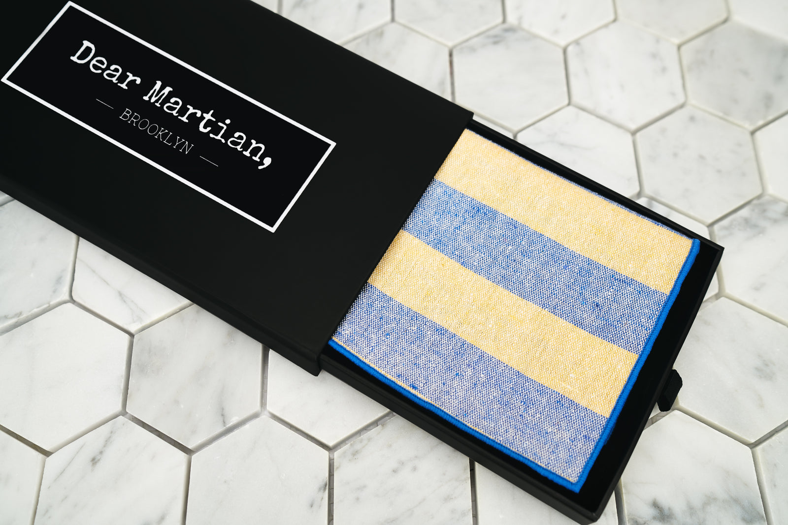 An image showing the Bookie yellow and blue striped pocketsquare. The matte black box features a pull out style with our Dear Martian, Brooklyn logo