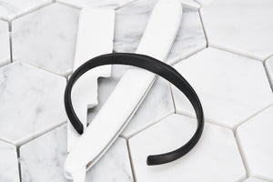 A top view product image of Dear Martian's pvd matte black cuff bracelet sitting against a white razor blade.