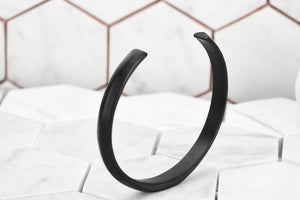 An image of the Duality matte black cuff bracelet for men facing up with a white hexagon background.