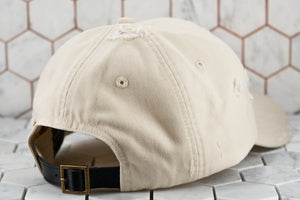 A back view of the tan dad hat by Dear Martian Brooklyn, which shows the leather belt buckle strap.