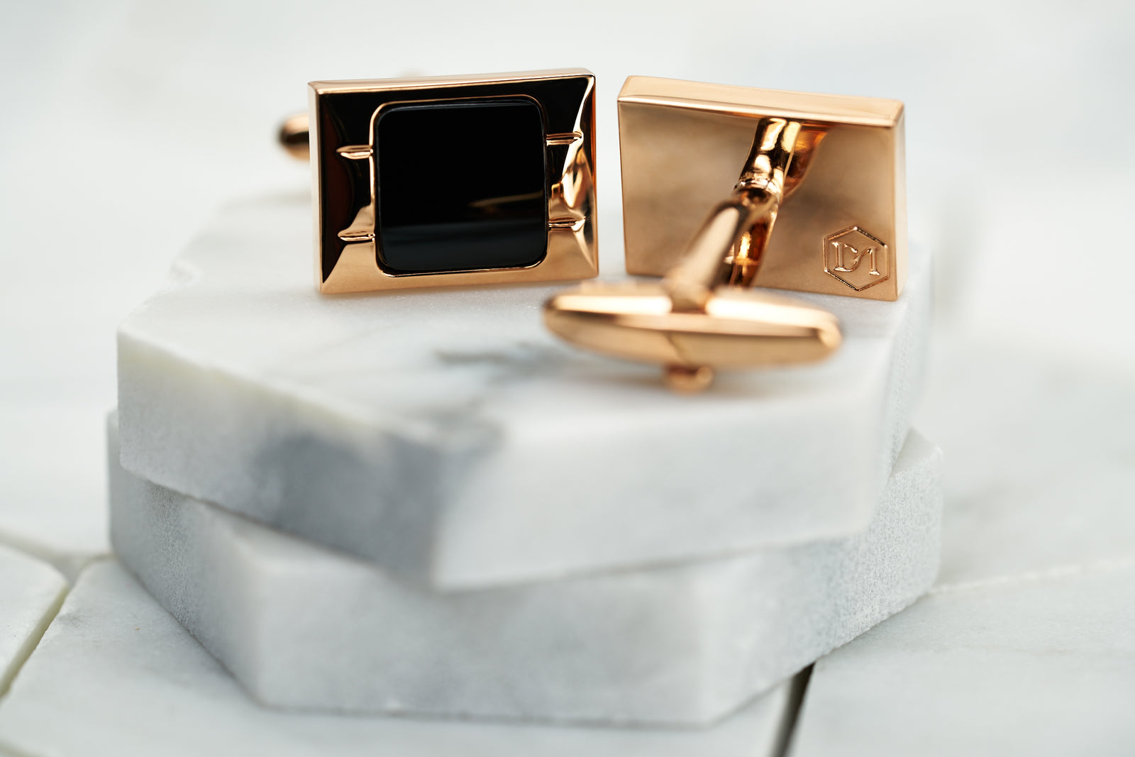 A product image featuring a pair of rose gold cufflinks by Dear Martian. The image depicts the front side, which has a solid black enameled center and the back of the cufflink, which shows the DM hexagon logo.