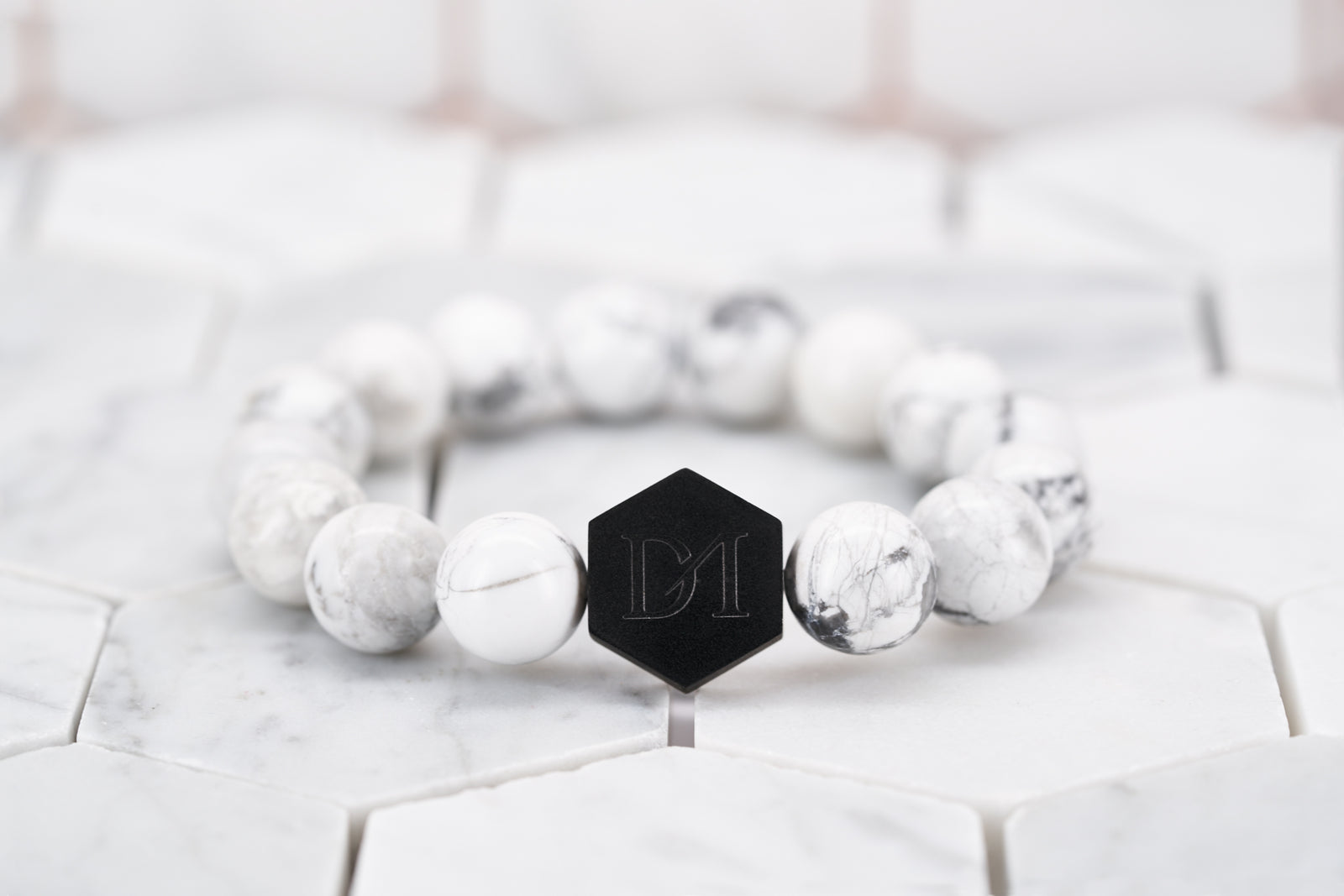 A front view image of the Dear Martian white howlite stone beaded bracelet with a black hexagon logo bead. The beaded bracelet is sitting on a white background.