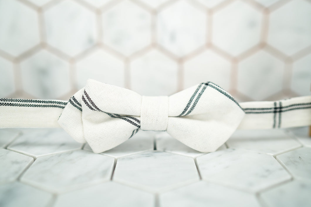 A front image of the Dear Martian Lexington ave white argyle pre-tied bow tie sitting against a white hexagonal background.