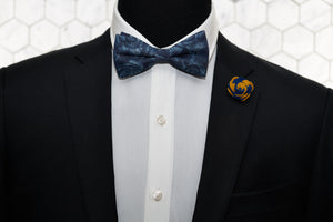A mannequin dressed in Dear Martian men's accessories; a blue denim floral patterned bow tie and a navy yellow flower lapel pin.