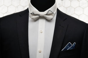 An image of a mannequin styled in Dear Martian accessories and a black suit jacket. Donning a diamond pointed white bow tie and cranford floral pocket square; the mannequin looks dapper.
