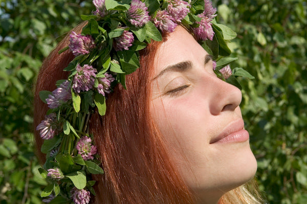 Redhead woman with flower crown on lush background, sun on her face