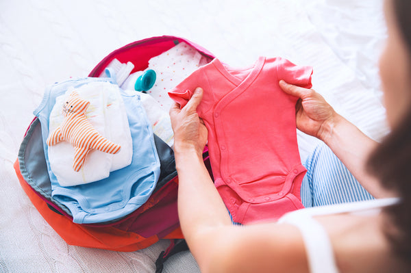 Pregnant woman packing bag for maternity hospital at home, getting ready for newborn birth, labor.