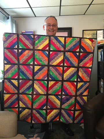 Brother holding quilt gifted from sister