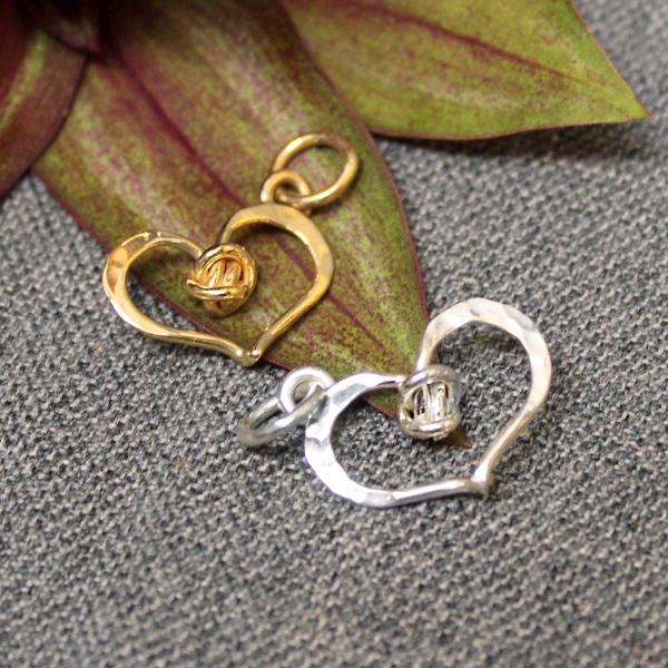 Hammered sterling silver and 14k gold heart shaped charm with love knot design in center.