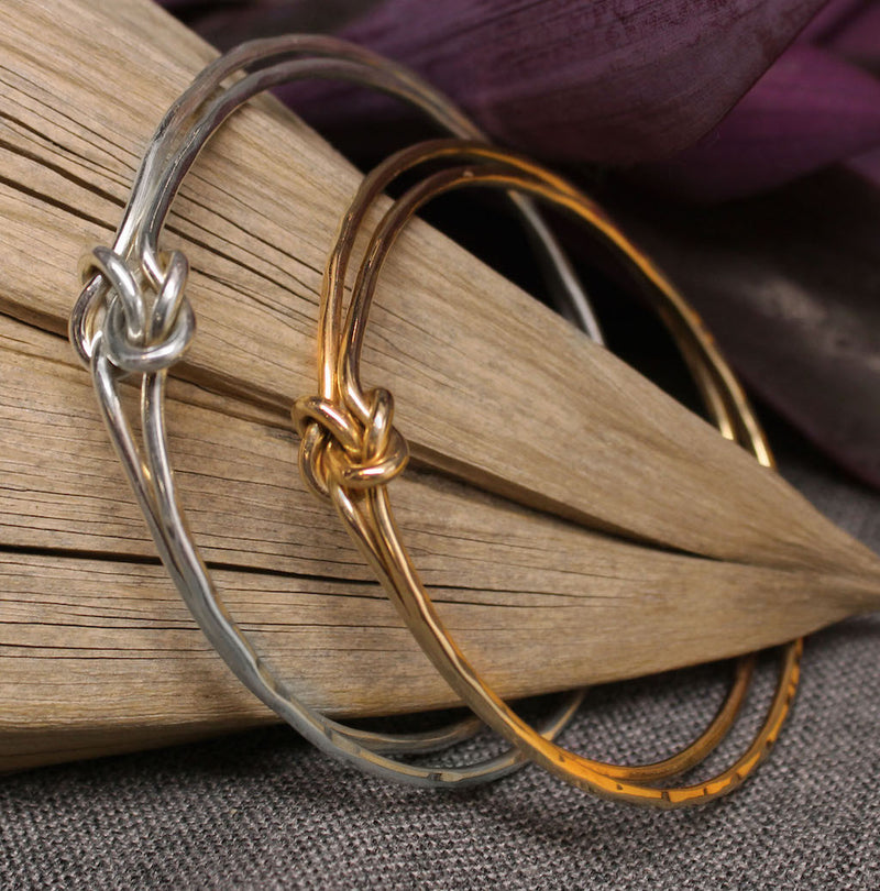 Sterling silver and gold bangles with friendship knot design in center.