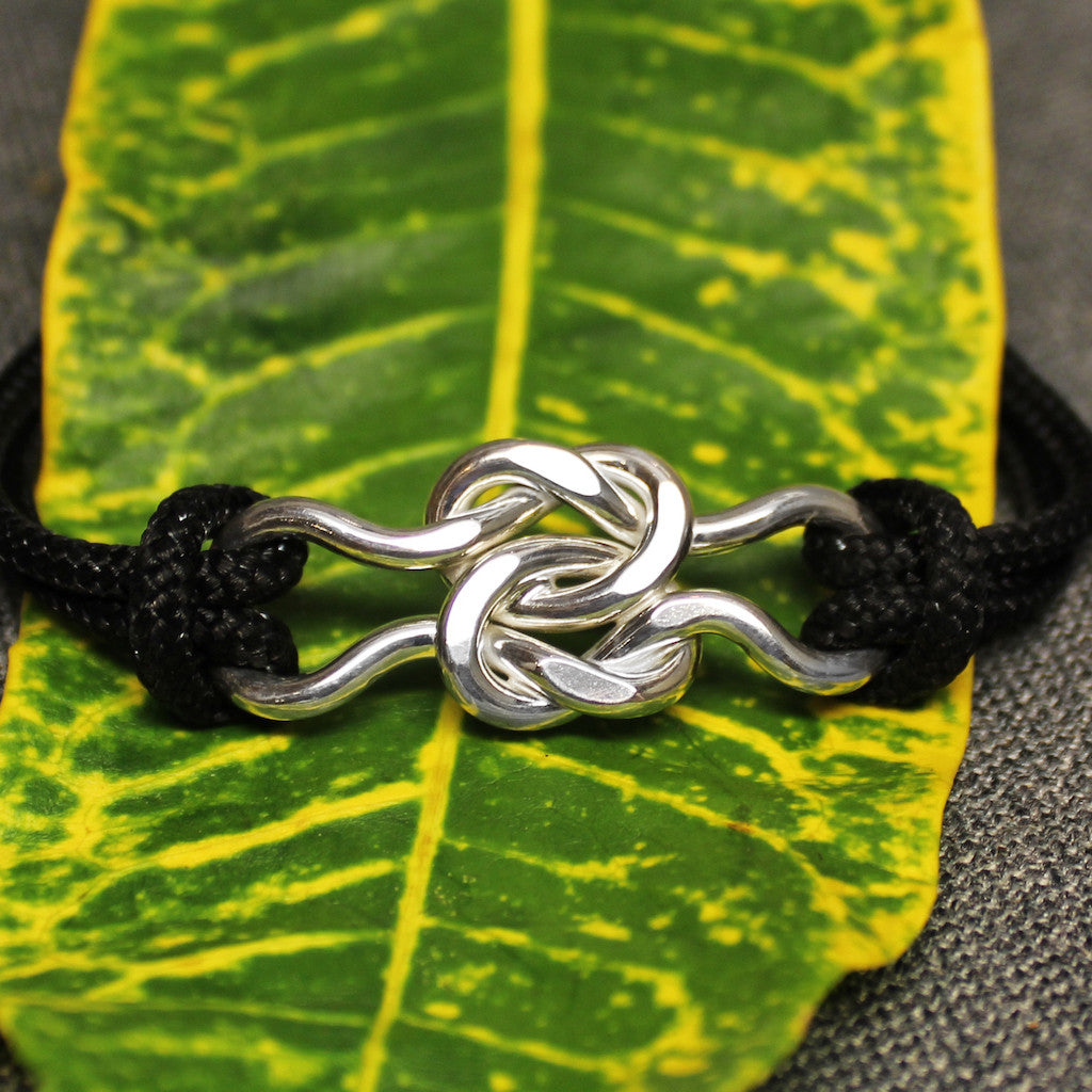 Black nylon adjustable cord friendship bracelet with sterling silver friendship knot design in center.