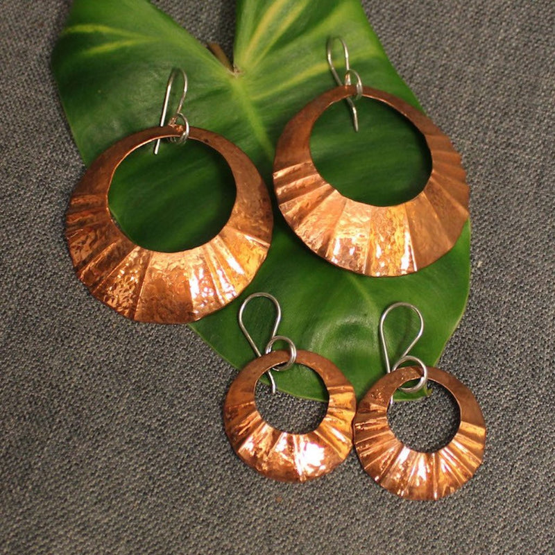 Small and large hammered circular copper earrings.