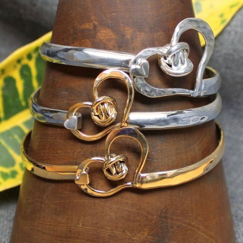 Sterling silver, 14k gold and 2-tone classic handcrafted bracelet with heart design and love knot in center.