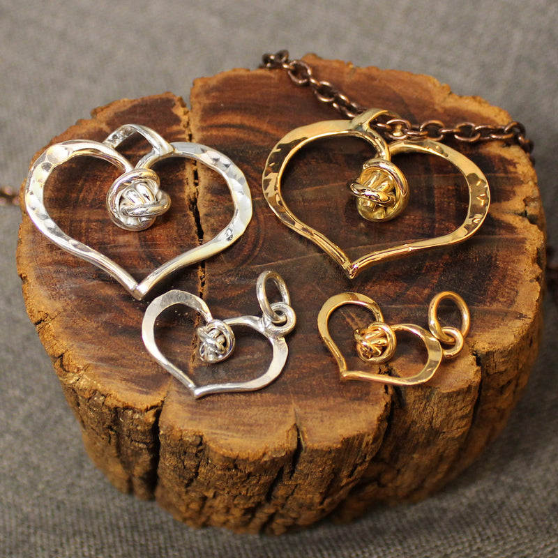 Sterling silver and 14k gold hammered heart shaped pendants with love knot design in center.
