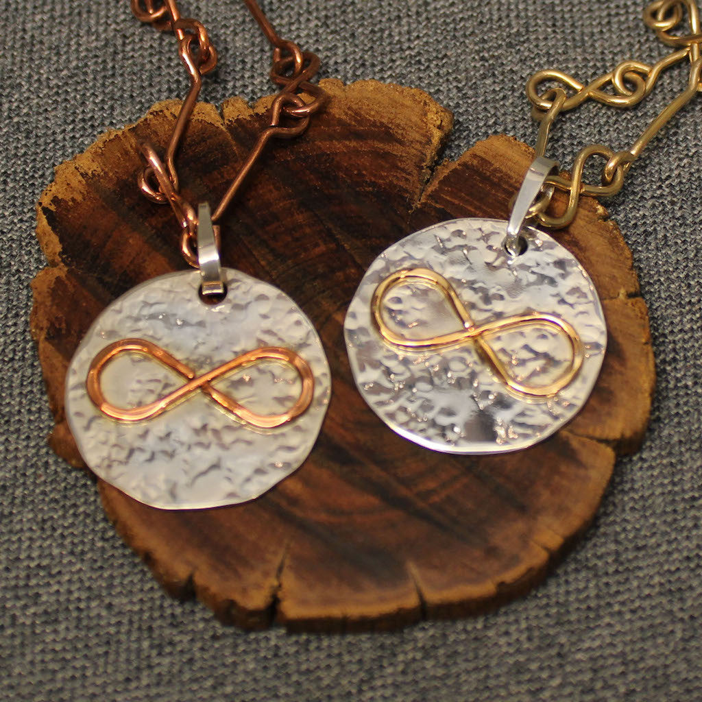 Hammered sterling silver disc pendant with copper or 14k gold infinity symbol in the center.