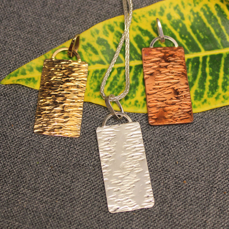 Copper, sterling silver and 14k gold pendants with hammered rectangular plate.
