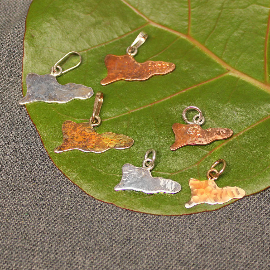 Handcrafted artisanal pendants and charms shaped like the map of St.Croix.