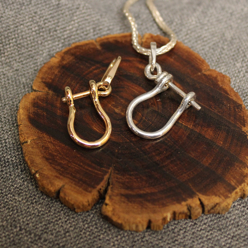 Sterling silver and 14k gold Sailor's Shackle pendants.