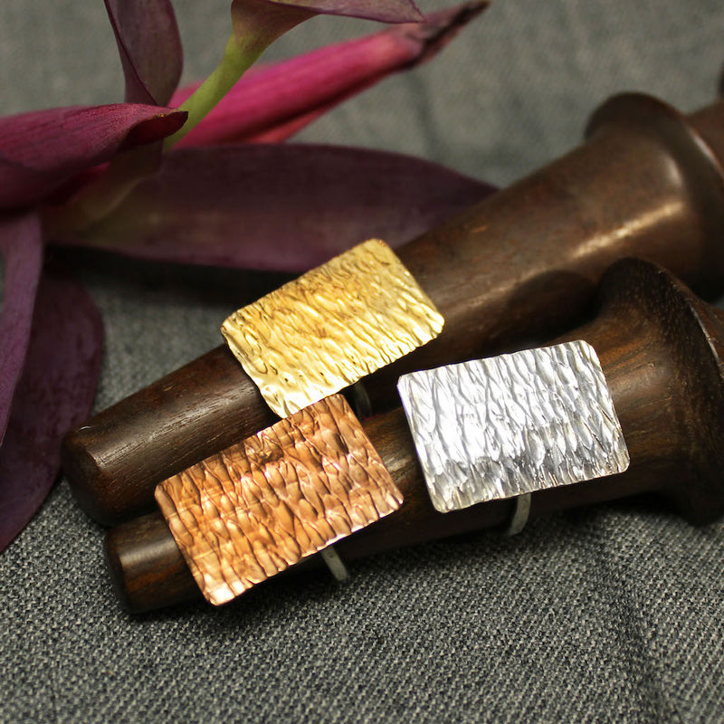 Copper, sterling silver and 14k gold rings with hammered rectangular plate.