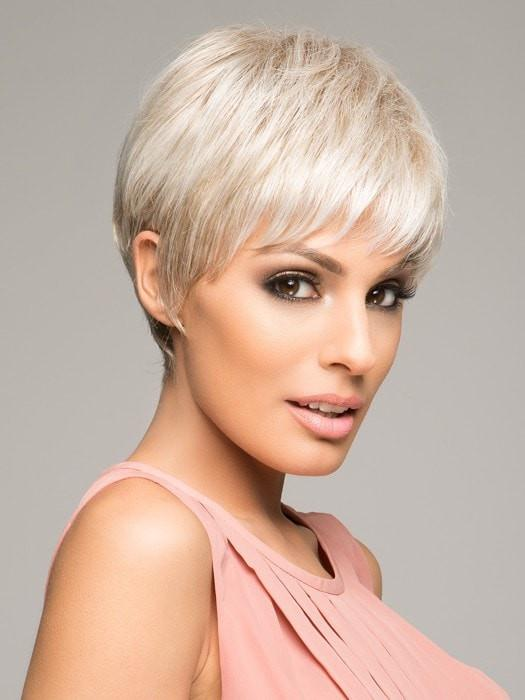This short wig has a wispy bang, textured layering on top with length at the crown and layered ends