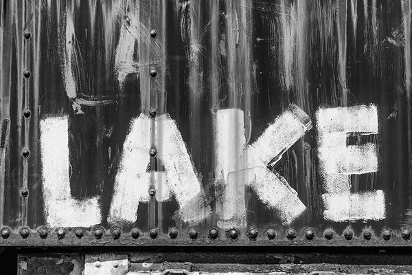 "Black and white detail photograph of the word ""LAKE"" painted with a brush onto the side of a rusty, abandoned train car."