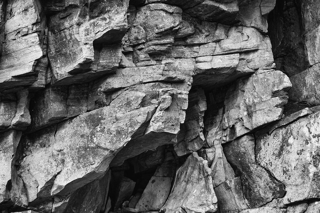 Black and white landscape photograph of dramatic, jagged layers of rock in the wall of a river canyon.
