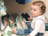 Cute baby playing with mommy's shoes