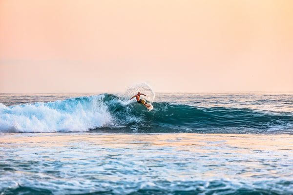 Professional surfer catching a wave while the sun is setting.