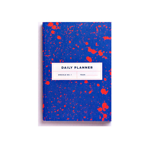 Daily planner book with coral red paint splatters on a bright blue background.